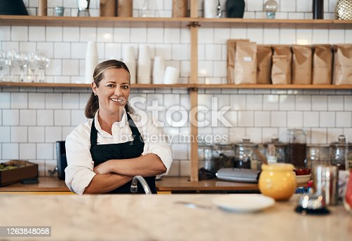 Portrait of a confident mature woman working behind the counter of a cafe