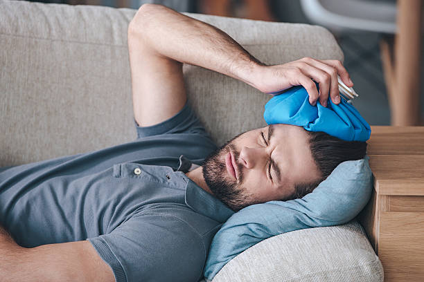 When you hit shelf with your head. Frustrated young man holding ice bag on his head while lying on the couch at home aftereffect stock pictures, royalty-free photos & images