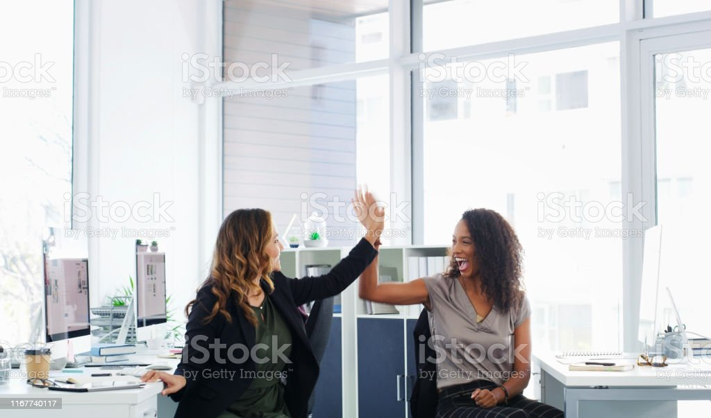 When you work together, you win together Shot of two young businesswomen giving each other a high five in a modern office Achievement Stock Photo