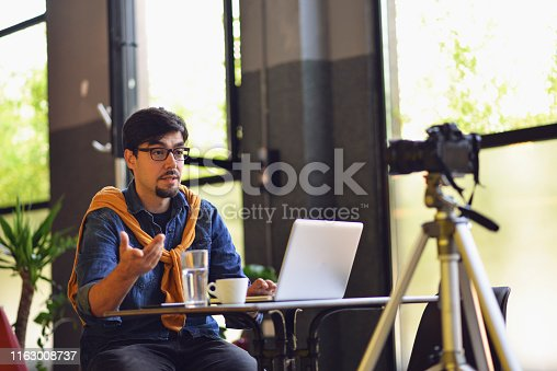 Man making video blog, is recording a new blog, laptop, coffee, life couch, life teacher