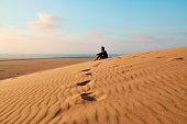Shot of a young man sitting on a hill in the Namibian Desert