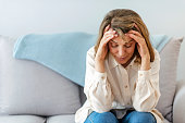 Photo of Woman suffering from stress or a headache grimacing in pain as she holds forehead with her hand, with copy space. Portrait of an attractive senior woman sitting on a sofa at home with a headache, feeling pain and with an expression of being unwell, with eyes closed.