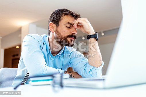 Young bearded businessman working on laptop computer while sitting in his home office. Business problems.