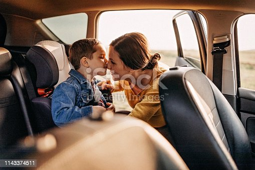 Pregnant mother preparing his son for travel in car