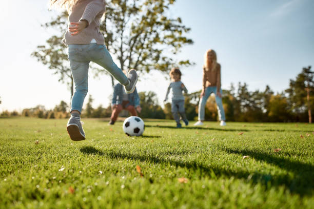 where family fun begins. happy family playing with a ball on meadow - parque público imagens e fotografias de stock