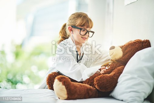 Shot of an adorable little girl dressed up as a doctor and examining a teddy bear with a stethoscope