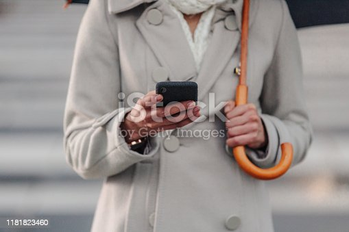 Cropped shot of an unrecognizable businesswoman texting on her cellphone while holding an umbrella outside in the rain