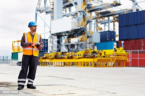 Shot of a young man in workwear using a digital tablet while standing on a large commercial dock
