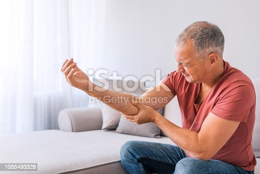 People, healthcare and problem concept - Photo of unhappy mature gray hair  man suffering from elbow pain at home while sitting on sofa during the day.