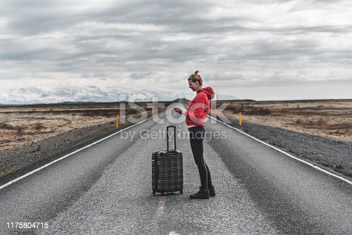 Woman in a red jacket with suitcase checking her phone on an empty road in a middle of nowhere.