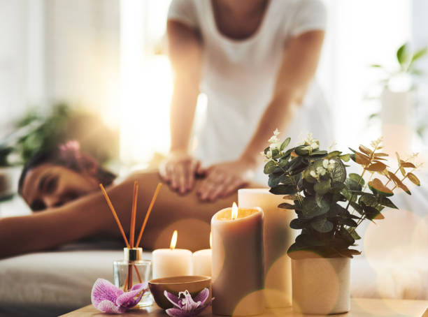 Where the world slows down Shot of spa essentials on a table with a woman getting a massage in the background aromatherapy stock pictures, royalty-free photos & images