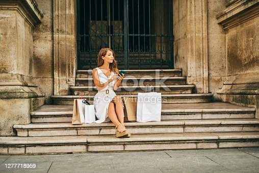 Shot of a beautiful young woman using a cellphone while out on a shopping spree in the city of Paris