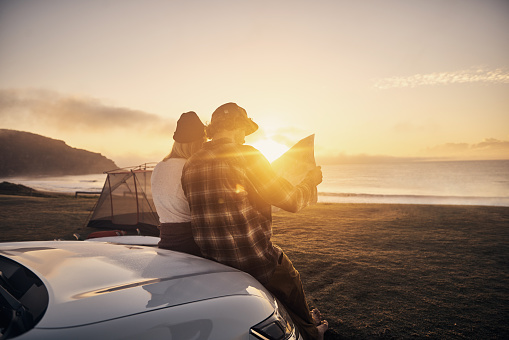 Shot of a young couple stopping by the beach to look at a map while on a roadtrip