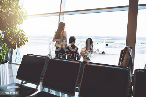 Single mother family waiting in departure area at the airport, for their flight. Traveling with children is not easy.