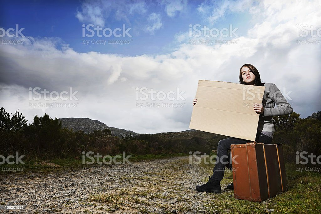Where to? Teenage hitchiker, desperate, holds blank destination sign royalty-free stock photo