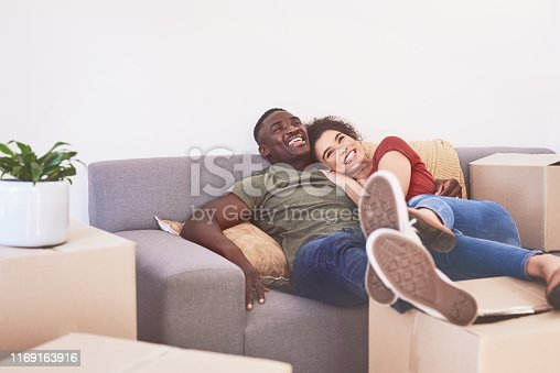 Shot of a happy young couple relaxing on a sofa in their new home