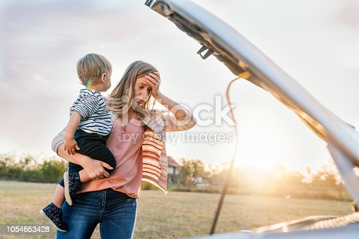 Portrait of young Caucasian woman standing by broken down car and waiting for assistance while holding her baby boy during sunset. Photo of female waits for assistance near her car broken down on the road side. Frustrated young brown hair woman looking at broken down car engine on street. Woman does not understand why her car engine failed. Desperate mother holding her angry baby.