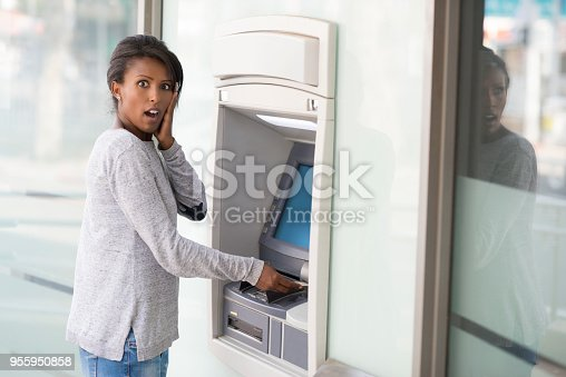 Young African woman looks surprised while getting money from the bank ATM machine. The woman looks in shock with hand on cheek.