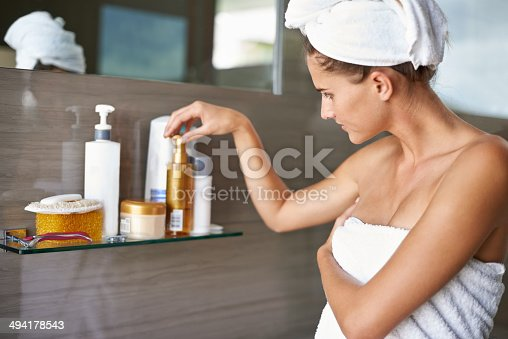 Shot of a woman wrapped on towels looking at bottles of cream in a bathroomhttp://195.154.178.81/DATA/i_collage/pi/shoots/783590.jpg
