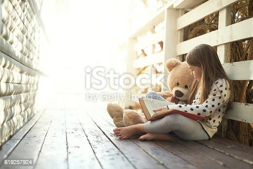 Shot of a little girl reading a book with her teddy bear beside her