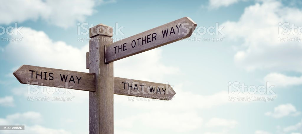 Which way to go road sign Crossroad signpost saying this way, that way, the other way concept for lost, confusion or decisions Decisions Stock Photo