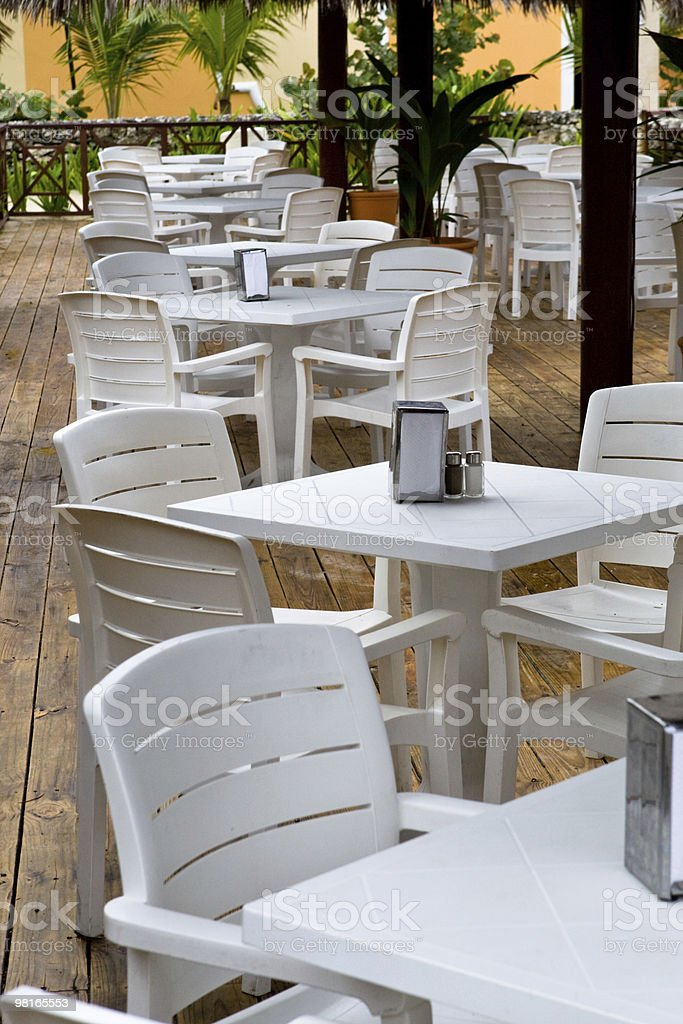 Whie plastic chairs and tables on the patio in cafe royalty-free stock photo