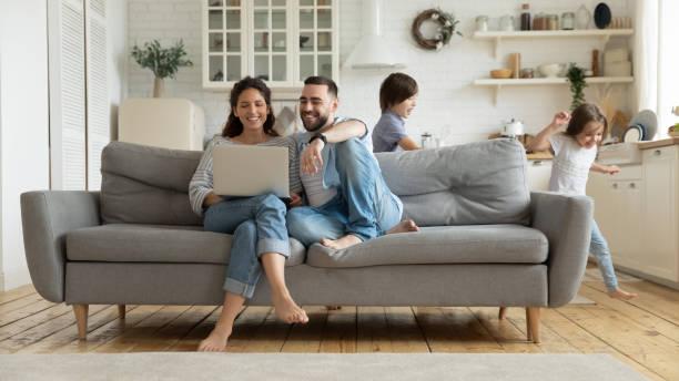 quando os miúdos ativos que funcionam pais que descansam no sofá usando o portátil - edifício residencial - fotografias e filmes do acervo