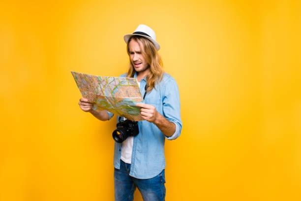 Mientras jornada triste y desilusionado hombre perdido el camino al hotel y ahora está mirando el mapa y tratando de definir el camino hasta el punto de destino - foto de stock