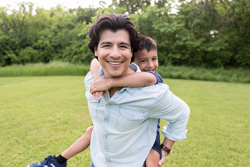 While uncle carries nephew, both smile for camera