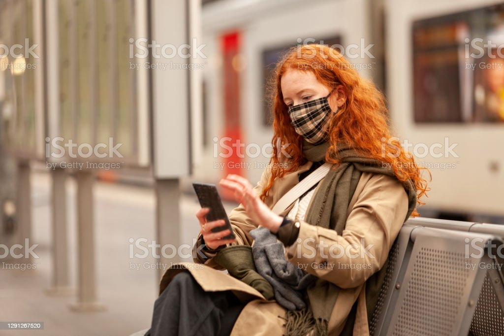 While waiting for her commuter train to arrive a young curly red haired student swipes on het mobile phone A female student with long curly red hair wearing a protective facial mask, in the city railway station. Spends time on her phone while waiting for her train to arrive. Dressed in stylish coat with matching scarf. 18-19 Years Stock Photo