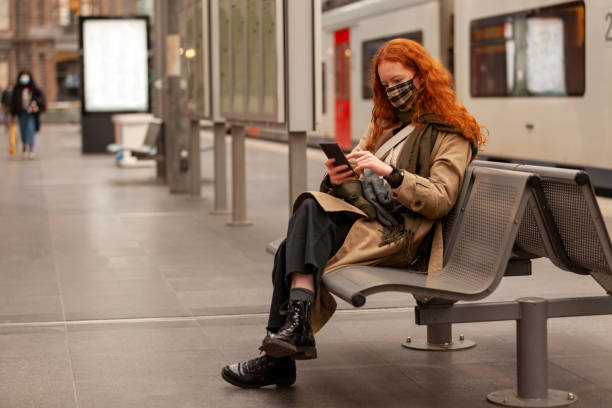 While waiting for her commuter train to arrive a young curly red haired student swipes on het mobile phone stock photo