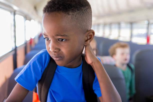 während er darauf wartet, aus dem bus zu steigen, macht sich der junge sorgen um die schule - schulkind nur jungen stock-fotos und bilder