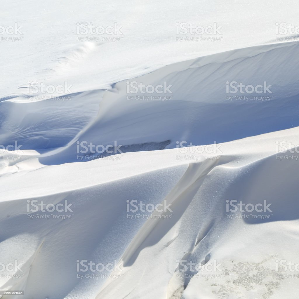 Whimsical big snowdrifts on a winter sunny day stock photo