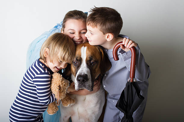 Whimsical Peter Pan Series isloated on white Three children dressed up as Wendy, John, and Michael from Peter Pan and hugging there dog nana peter pan stock pictures, royalty-free photos & images