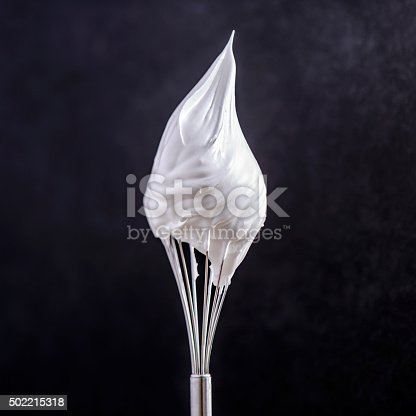 whip cream on top of whisk on black background