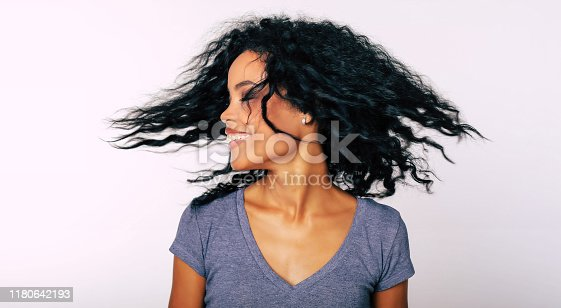 910856488 istock photo I whip my hair back and forth. Charming Afro-American lady with frizzy dark hair is whipping her hair with her eyes closed while laughing with joy. 1180642193