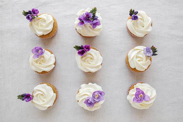 whipped cream frosting vanilla cupcakes with purple edible flowe - hausgemachte hochzeitstorten stock-fotos und bilder