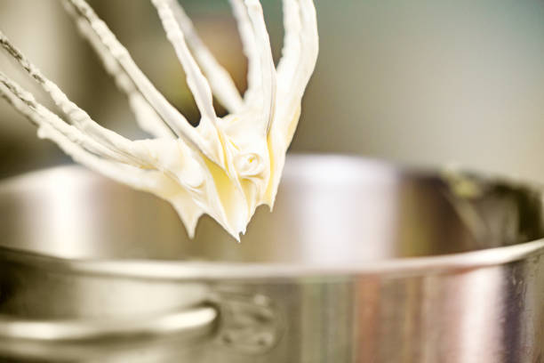 Whipped cream hanging on electric mixer whip Whipped cream hanging on electric mixer's whip electric mixer stock pictures, royalty-free photos & images