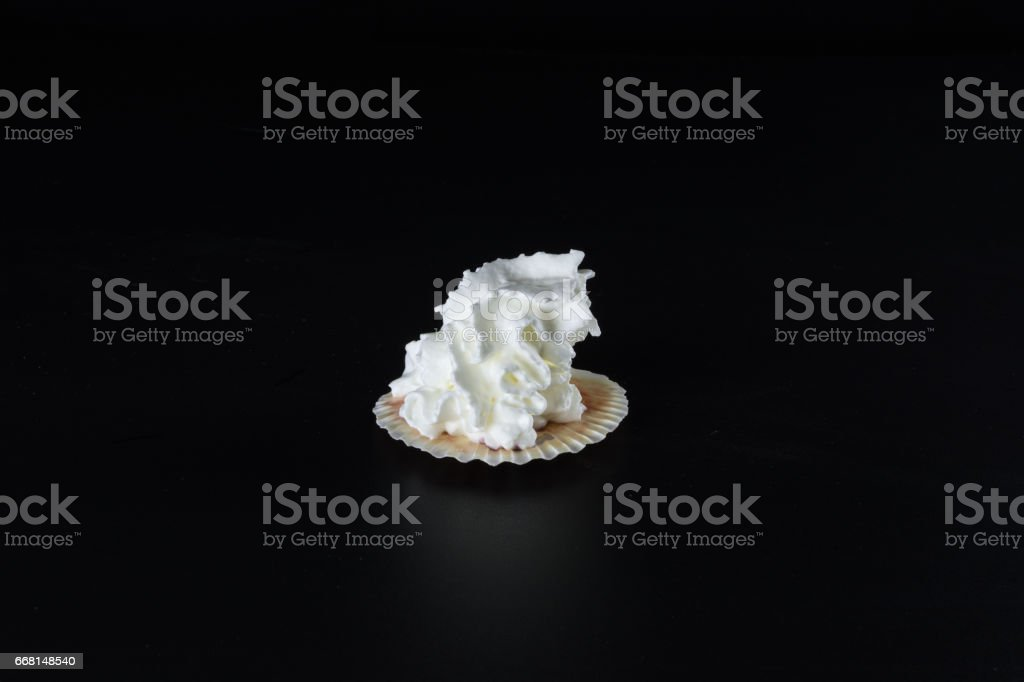 0a5be9172 Whipped cream in a sea shell on a black background royalty-free stock photo
