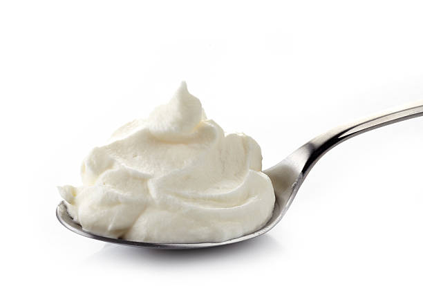 whipped cream in a spoon whipped cream in a spoon on white background buttercream stock pictures, royalty-free photos & images
