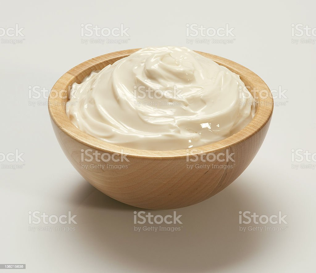 Whipped cream in light wooden bowl on white backing royalty-free stock photo