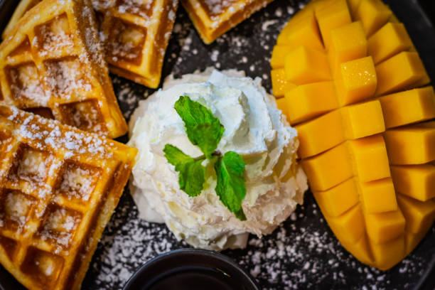 Whipped cream, mint leaf, mango and waffles sprinkled with powdered sugar served on a black plate – zdjęcie