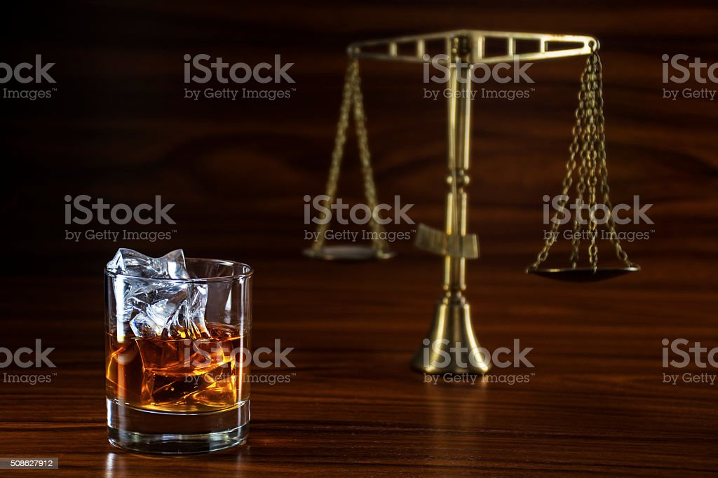 whiskey  and blurred scales of justice, concept alcohol and law stock photo