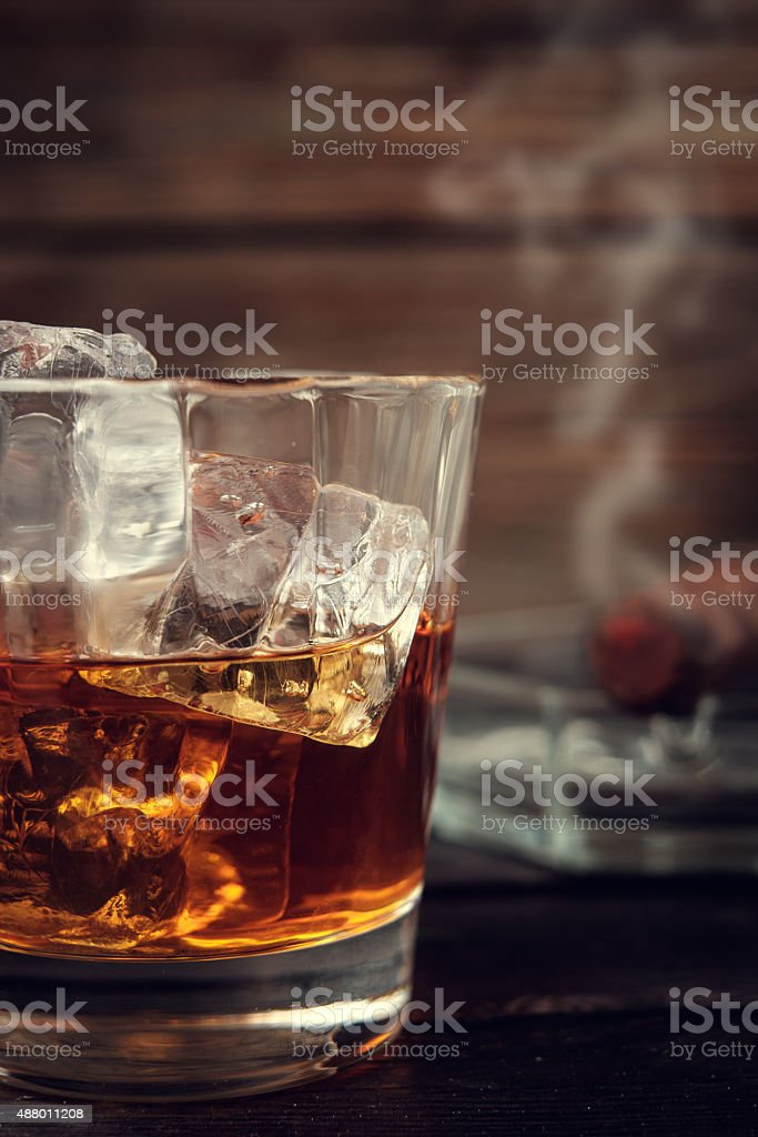 Whiskey and cigar on wooden background stock photo