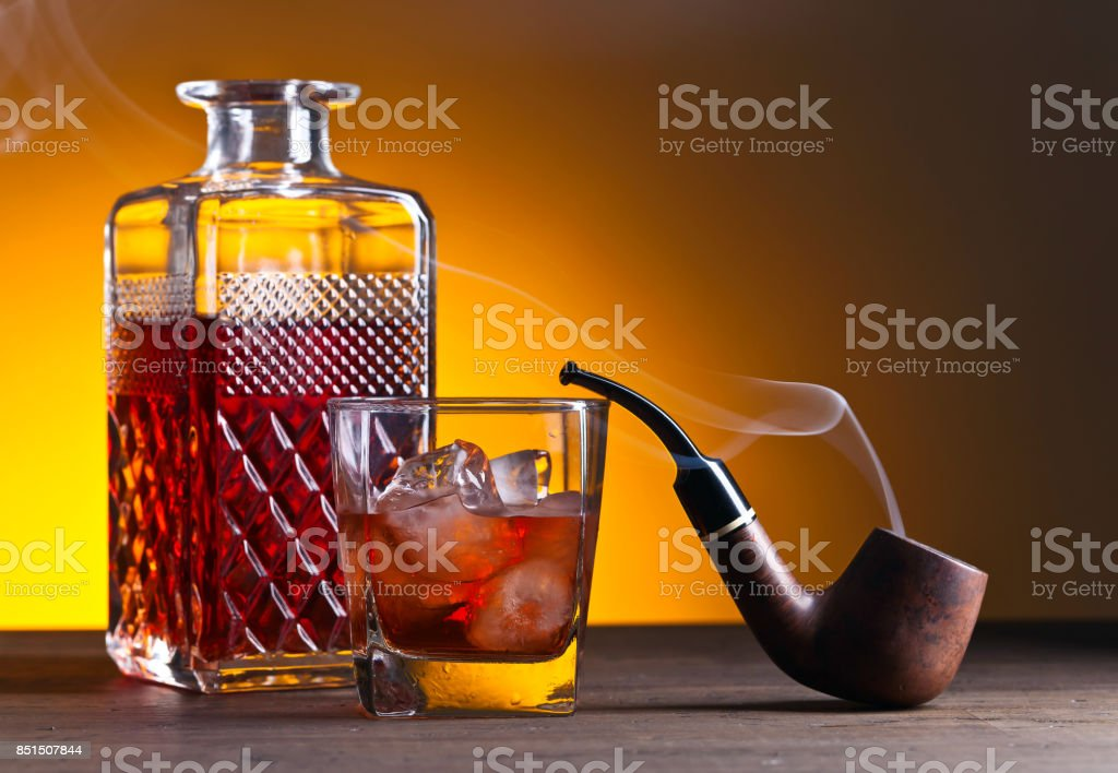 whiskey and pipe on a old wooden table,copy space for your text stock photo