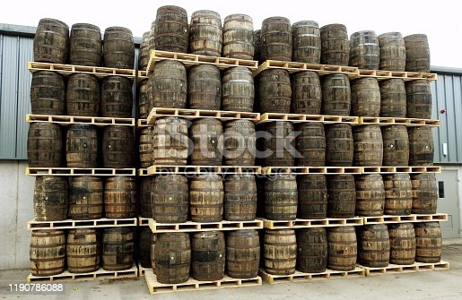 Wooden whiskey or wine ageing barrels stacked on pallets outdoors.