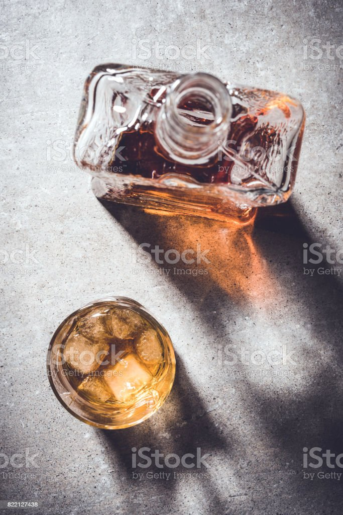 Whiskey bottle and whiskey glass on gray stone table. stock photo