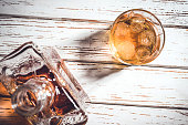 Whiskey bottle and whiskey glass with ice cubes on white wooden table. Close up