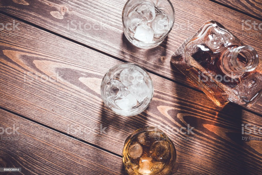 Whiskey bottle and whiskey glasses with ice cubes. stock photo