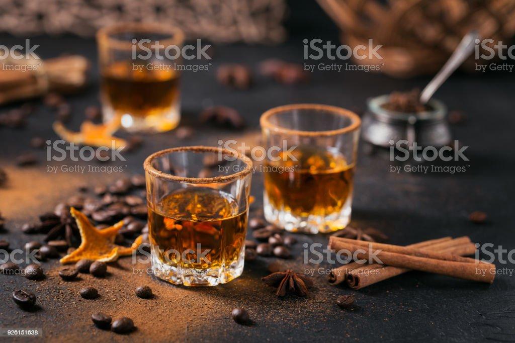 Whiskey, brandy or liquor, spices, anise stars, coffee beans, cinnamon sticks stock photo